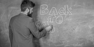 Man bearded teacher missed his work during vacation. Teacher near chalkboard holds chalk write inscription back to. School. Back to school concept. Teacher royalty free stock photography