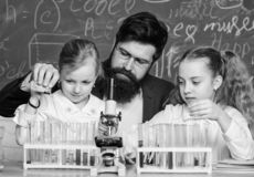Man bearded teacher work with microscope and test tubes in biology classroom. How to interest children study. Explaining royalty free stock photography