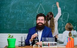 Man bearded teacher work with microscope and test tubes in biology classroom. Biology plays role in understanding of. Complex forms of life. School teacher of royalty free stock photos