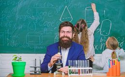 Man bearded teacher work with microscope and test tubes in biology classroom. Biology plays role in understanding of. Complex forms of life. School teacher of royalty free stock image