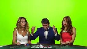 Man beat two beautiful girls in card. Green screen studio stock footage