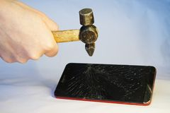 A man beats a hammer on the screen of a smartphone. Features of breakage, warranty and repair royalty free stock photos