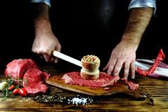 The man beats the meat with a wooden hammer. The man beats the meat with a  hammer Royalty Free Stock Image