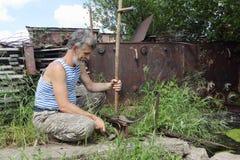 The man beats off scythe a hammer. In a garden stock photos