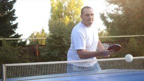 Man beats tennis balls playing table tennis game in the yard in slow motion outdoor close-up in sunny day. stock photo
