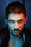 Man with beautiful eyes. Man in leather jacket. Piercing eyes. Husky eyes. Dramatic portrait of tinted red and blue filter. Fashionable style Royalty Free Stock Photo