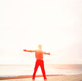 A man with a beautiful figure standing arms outstretched and sighs sea air Royalty Free Stock Photos