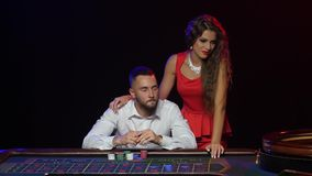 Man and beautiful girl in the casino wins in roulette stock footage