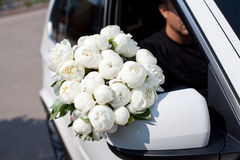 Man with beautiful white peony in the car waiting a girl. Royalty Free Stock Photos