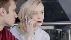 Man and a beautiful woman make an order by phone to delivery department. Female blonde model tells her friend about conversation with support service on stock footage