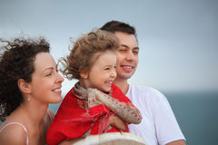 Man and beautiful woman protects girl from wind. Young man and beautiful woman protects little girl from wind on seacoast Stock Images