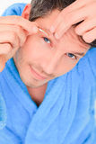 Man beauty. Male cosmetic treatment removing hairs with tweezing Royalty Free Stock Image