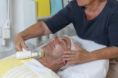 Man at beauty center receiving facial treatment Stock Photo