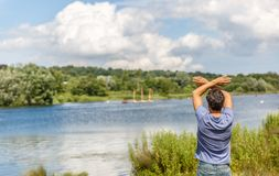 A man beckons from the shore of a great river stock photography