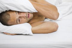 Man in Bed. Man trying to sleep with a pillow over his head Royalty Free Stock Photos