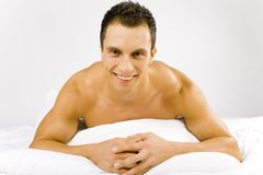 Man in the bed. Smiled and happy man lying on the bed. White background in studio royalty free stock photography
