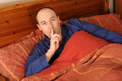 Man in Bed. A man laying in bed with blue pajamas signals for quiet with his finger to his lips Royalty Free Stock Photo