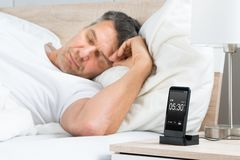 Man on bed with alarm on a cell phone display Stock Photos