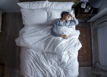 Man on bed alone with a headache Stock Images