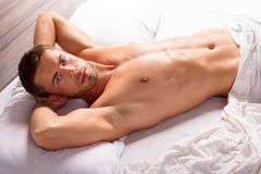 Man in bed. Attractive young man laying in bed Stock Photos