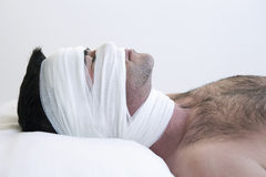 Man in bed with bandages Royalty Free Stock Photography