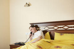 Man in bed calling by phone stock photography