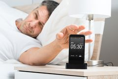 Man on bed with cell phone. Mature Man On Bed With Cell Phone On Nightstand Royalty Free Stock Image