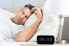 Man on bed with clock on nightstand. Mature Man Sleeping On White Bed With Clock On Nightstand Stock Images