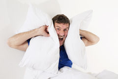Man in bed covering his ears Royalty Free Stock Photography