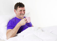Man in bed with cup Stock Photo