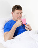 Man in bed with cup Royalty Free Stock Images