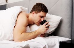 Man in bed drinking coffee. Royalty Free Stock Images