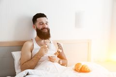 Man in bed drinking morning coffee with croissant Stock Image