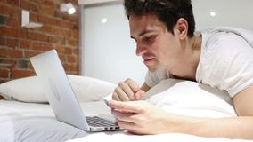Man in Bed Excited for Successful Online Shopping, Transaction. 4k , high quality stock video