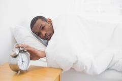Man in bed extending hand to alarm clock Stock Photos