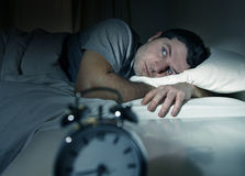 Man in bed with eyes opened suffering insomnia and. Young man in bed with eyes opened suffering insomnia and sleep disorder thinking about his problem stock photography