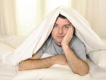 Man in bed with eyes opened suffering insomnia and Stock Images