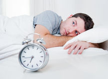 Man in bed with eyes opened suffering insomnia and Stock Photos
