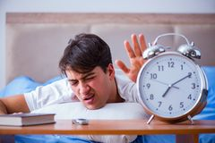 Man in bed frustrated suffering from insomnia with an alarm cloc Royalty Free Stock Photos