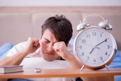 Man in bed frustrated suffering from insomnia with an alarm cloc Royalty Free Stock Photo
