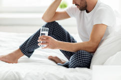 Man in bed with glass of water at home. People, bedtime and rest concept - man in bed with glass of water at home Royalty Free Stock Image