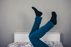 Man in bed with his legs raised Royalty Free Stock Photos