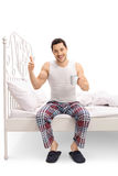 Man on bed holding cup and giving a thumb up Stock Images