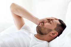 Man in bed at home suffering from headache Royalty Free Stock Photography