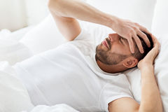 Man in bed at home suffering from headache Stock Image