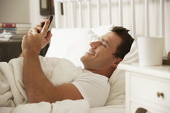 Man In Bed At Home Texting On Mobile Phone Royalty Free Stock Images