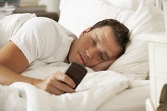 Man In Bed At Home Texting On Mobile Phone Stock Images