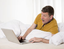 Man in bed with laptop Stock Photo