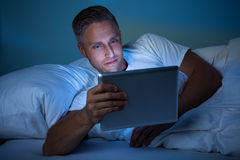 Man On Bed Looking At Digital Tablet Royalty Free Stock Image