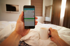 Man In Bed Looking At Health Monitoring App On Mobile Phone Stock Photo